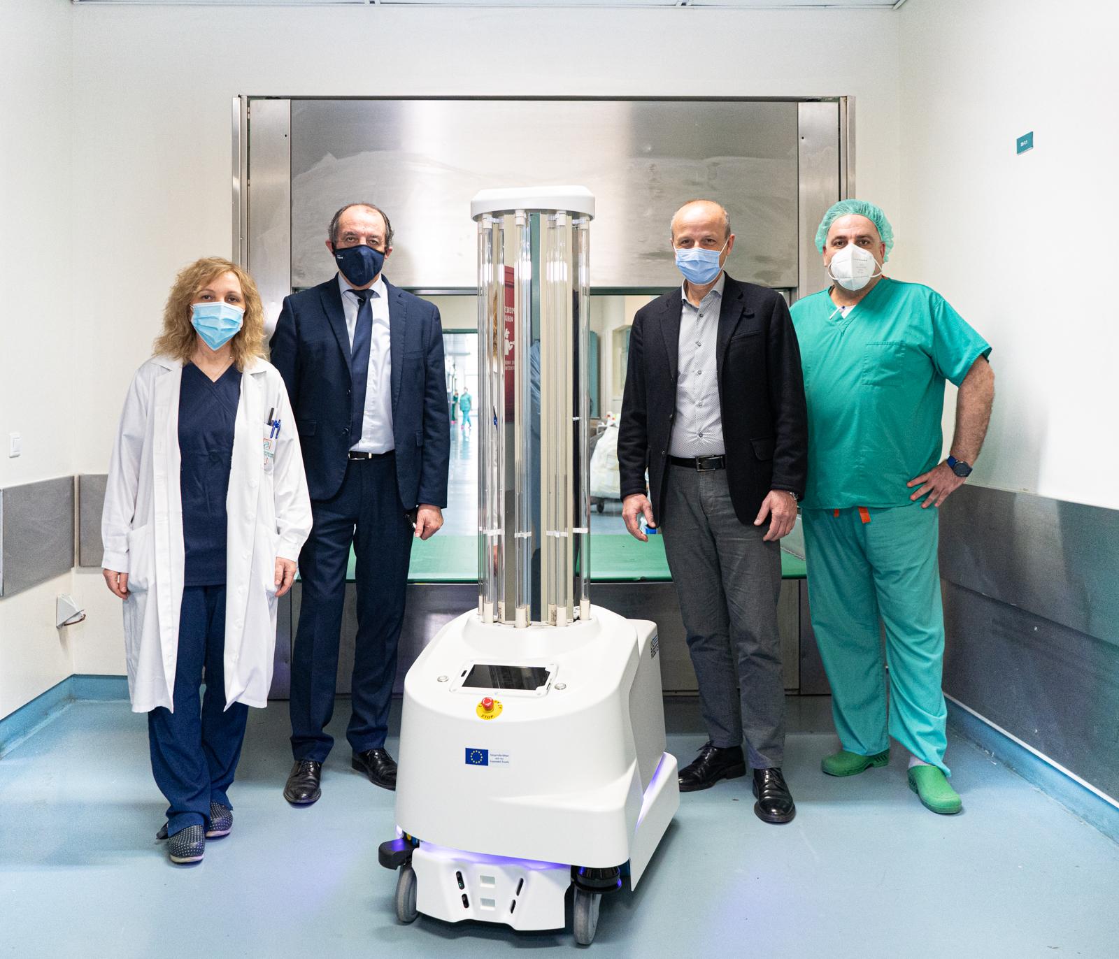 Η πρόεδρος της Επιτροπής Νοσοκομειακών Λοιμώξεων και συντονίστρια Covid-19 Κωστούλα Αρβανίτη, ο Γενικός Διευθυντής Κωνσταντίνος Εμμανουηλίδης, ο Πρόεδρος ΔΣ Μιχάλης Καραβιώτης και ο προϊστάμενος χειρουργείων Σάββας Μαυροματίδης, μαζί με το ρομπότ Τάλως στην είσοδο των κεντρικών χειρουργείων